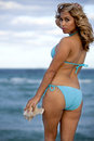 Pretty woman in light blue bikini holding a shell with ocean background Stock Photos