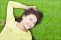 Pretty woman listening music and lying on a meadow Stock Photos