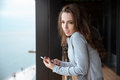 Pretty woman listening to music standing on the balcony young weared in gray top Royalty Free Stock Photo