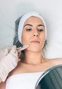 Pretty woman looking lips treatment in a mirror closeup of young beauty medicine healthcare and beauty concept Royalty Free Stock Photography