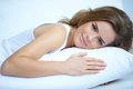 Pretty woman lying prone on white pillow close up young laying while looking at the camera Royalty Free Stock Images