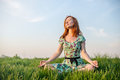 Pretty woman meditate in the park sitting on grass Royalty Free Stock Images