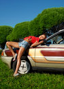 Pretty woman pin-up style lay on retro car Stock Image