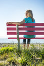 Pretty woman on pink bench attractive blonde wearing jeans and a turquoise top sitting a overlooking the pacific ocean looking Royalty Free Stock Image