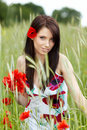 Pretty woman in poppy flowers Stock Photography