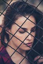 Pretty woman portrait behind fence shot in the city Royalty Free Stock Photo