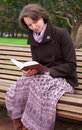 Pretty woman reading a book on a bench Stock Images
