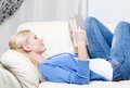 Pretty woman reads the book lying on the sofa Royalty Free Stock Photography