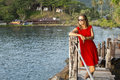 Pretty woman in a red dress and sunglasses looks at the water with wooden planks. Royalty Free Stock Photo