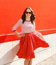 Pretty woman in red sunglasses and dress against the colorful Royalty Free Stock Photo