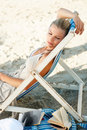 Pretty woman relaxing on a deck chair by the beach Royalty Free Stock Photo