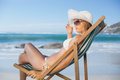 Pretty woman relaxing in deck chair on the beach a sunny day Stock Photos