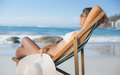 Pretty woman relaxing in deck chair on the beach a sunny day Royalty Free Stock Images