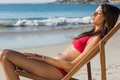 Pretty woman relaxing on her deck chair the beach Stock Photography