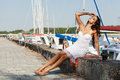 Pretty woman on the sea background beautiful in white dress sitting in hot sun pier near boats and yachts outdoors lifestyle Royalty Free Stock Photography