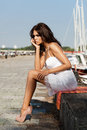 Pretty woman on the sea background young sexy in white dress sitting in hot sun pier near boats and yachts outdoors lifestyle Royalty Free Stock Photo