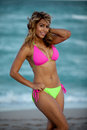 Pretty woman in sexy colorful bikini pink and lime green with ocean the background nlooking at camera and smiling Stock Images