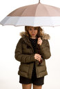Pretty woman sheltering under her umbrella Stock Images