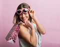 Pretty woman with a shopping bag pink glasses and Royalty Free Stock Images
