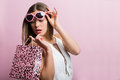 Pretty woman with a shopping bag pink glasses and Stock Photo