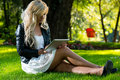 Pretty woman sitting on the grass with digital tablet lying Stock Photo