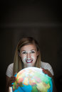 Pretty woman smiling while using an earth globe young blond a lit in the dark showing east africa the middle east and asia Royalty Free Stock Photo