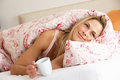 Pretty Woman Snuggled Under Duvet With Hot Drink Stock Photography