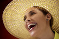 Pretty woman with straw hat smiling at camera mid adult and looking up on red background Royalty Free Stock Photo