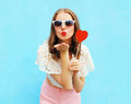 Pretty woman in sunglasses with red heart lollipop sends an air kiss over colorful blue Royalty Free Stock Photo