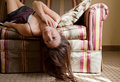 Pretty Woman Upside Down on Couch Royalty Free Stock Photography
