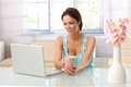 Pretty woman using laptop at home young computer sitting table drinking tea Royalty Free Stock Images