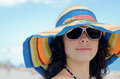 Pretty woman wearing a colourful closeup portrait of brunette sunhat and sunglasses on beach Royalty Free Stock Photography