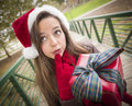 Pretty Woman Wearing a Santa Hat with Wrapped Gift Royalty Free Stock Image