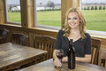 Pretty woman in winery or bar with red wine a blonde drinks merlot a beautiful brown woodwork surrounding her she appears to be Stock Photography
