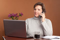 Pretty woman working at home brunette or shopping a laptop on the kitchen table with a cup of coffee talking on the phone looking Royalty Free Stock Images