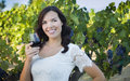 Pretty young adult woman enjoying a glass of wine in vineyard mixed race the Stock Image