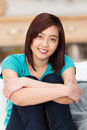 Pretty young asian student with a sincere smile sitting her knees drawn up and folded arms looking directly at the camera Royalty Free Stock Photography