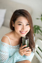 Pretty young asian woman holding green fresh vegetable juice or Royalty Free Stock Photo