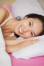 Pretty young asian woman lying in her bed smiling at the camera home bedroom Stock Image