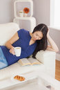 Pretty young asian woman lying on the sofa reading a book holdin holding her coffee in living room at home Stock Photos