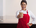 Pretty young barista offering cup of coffee to go smiling at camera in a cafe Stock Photography