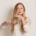 Pretty young blond girl brushing her hair portrait of a in a white dress long with a purple brush isolated against a light grey Royalty Free Stock Images