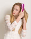 Pretty young blond girl brushing her hair portrait of a in a white dress long with a purple brush isolated against a light grey Royalty Free Stock Photo