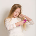 Pretty young blond girl brushing her hair portrait of a in a white dress long with a purple brush isolated against a light grey Stock Photography