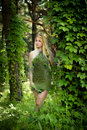 Pretty young blonde girl with long hair in green dress like an elf standing in the green forest where trees are enlaced with liana Royalty Free Stock Photo