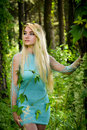 Pretty young blonde girl with long hair in turquoise dress standing in the green forest Royalty Free Stock Photo