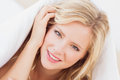 Pretty young blonde smiling at camera from under the duvet home in bedroom Royalty Free Stock Photo