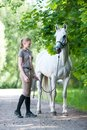 Pretty young blondy teenage girl with her favorite white horse.