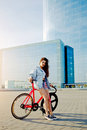 Pretty young brown haired woman standing with her modern pink bicycle in city Royalty Free Stock Photo