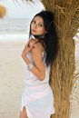 Pretty young brunette on a beach near the palm tree Royalty Free Stock Images